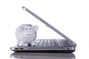 Piggybank over a modern laptop, the cost of technology and information (isolated on white)