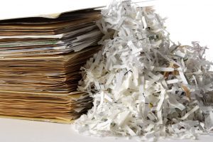 Shredded documents with stacked of with folder isolated on white background.