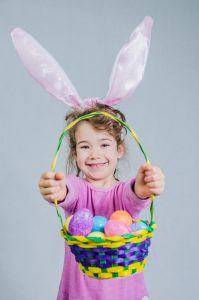 Little girl wearing pink shirt and easter bunny ears. She holds holds a basket of easter eggs in front of camera.