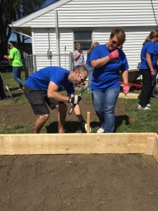 Corey Cates and Rebecca Price pound a stake that will keep the raised bed in place.