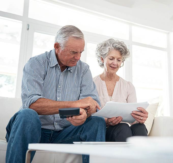 A retired couple looking over some papers